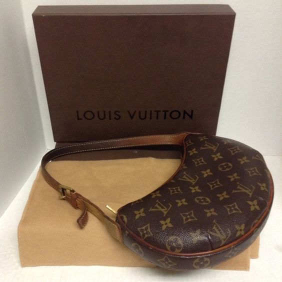 """The Louis Vuitton Monogram Canvas Croissant PM . The Louis Vuitton Monogram Canvas Croissant PM . Pre-owned In Good Condition The exterior is clean and beautiful. The leather handle and trim have turned a nice honey patina with signs darkening &creasing to the handle. The gold-tone hardware has light  scratches &fading,as normal.The interior needs to be clean which I don't know how and won't attempt please see photos. There's no tips ,tears, &the piping great. Measures approx 10""""x6"""" handle…"""