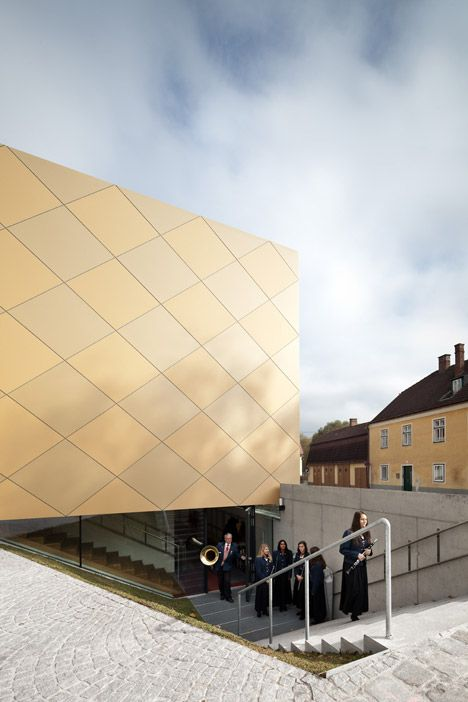 Vienna-based studio Franz Architekten references brass instruments with this golden music hall in Austria, clad with a diagonal grid of square aluminium panels.: