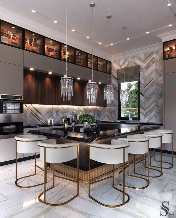 Поверхность стола выполнена из мрамора «Black Moon». Ансамбль цветовых акцентов достигается использованием латунных вставок в мраморе фартука и строгих линий барных стульев, также выполненных из латуни.