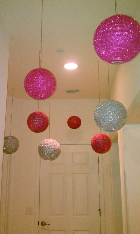 used spray glue on the paper lanterns then sprinkled glitter on them.