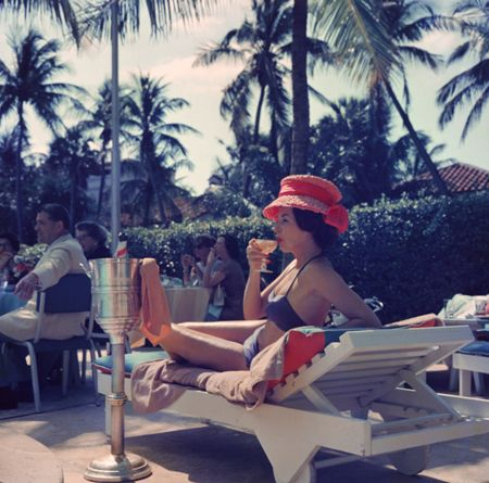 A woman watching a poolside fashion show at the Colony Hotel, Palm Beach, Florida, 1961. Slim Aarons: