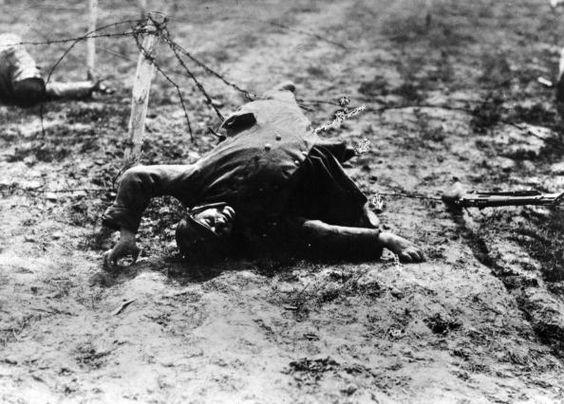 WW1 dead French soldier lying across German barbed wire © Getty