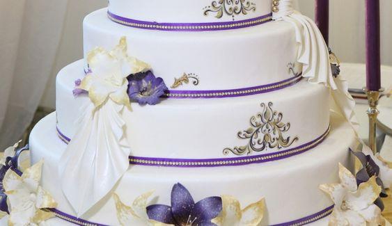 Tort nunta cu falduri si crini N329: tort de nunta din martipan alb pictat, decorat cu flori de crin comestibile, falduri din martipan si panglici si strasuri necomestibile.