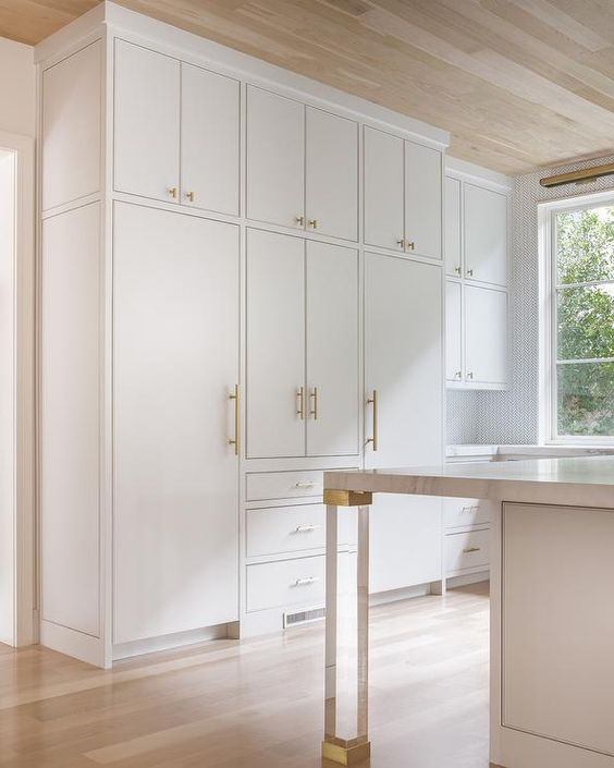 Brass and lucite legs, placed on gray wash wood floors under an oak plank ceiling, accent a white island topped with a gray and white marble countertop facing white concealed fridges placed both under and on either side of white flat front cabinets adorning Lewis Dolan Bar Pulls and Knobs.