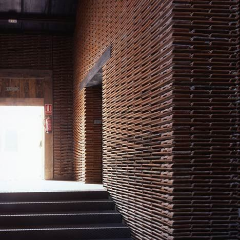 stacks of reclaimed roof tiles form walls inside this