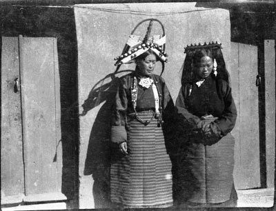 Phot: Lt Col R. S. Kennedy? Willoughby Patrick Rosemeyer?, Coll: Sir Charles Bell, Date: 1920-1921 or 1922, Region: Lhasa,  Mrs Taring (left) and Mrs Pemba (right) in Fort at Gyantse. Mrs Taring wears elaborately decorated headdress typical of Gyantse region, while Mrs Pemba wears that typical of Lhasa region. Both wear jewellery such as gau amulet boxes around their necks and other items. Photograph demonstrates very well regional differences in aristocratic women's dress in Central Tibet.