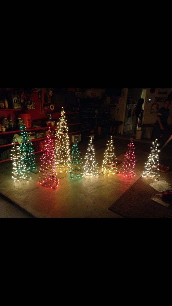Christmas Yard Decor. Trees made out of tomato cages and mini lights.