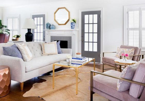 Chic living room features a light gray linen tufted sofa facing a pair of pink accent chairs lined with yellow and gray damask pillows across from a brass and mirror coffee table, Worlds Away Gold Leaf Sabre Leg Coffee Table with Mirror Top, atop a brown cowhide rug.