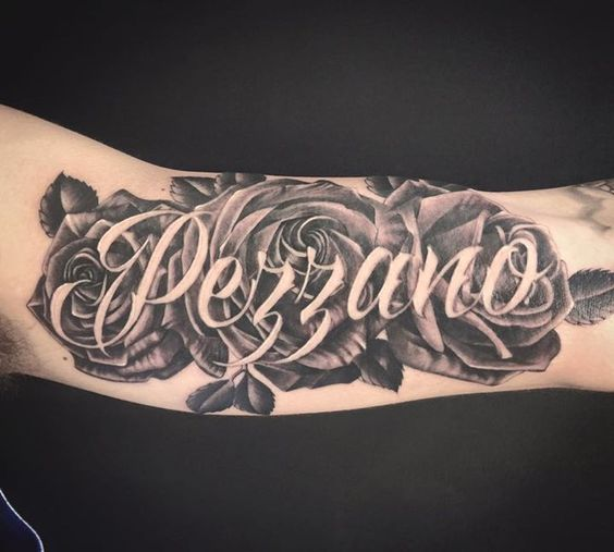 Black and grey roses tattoo with last name across. On the arm