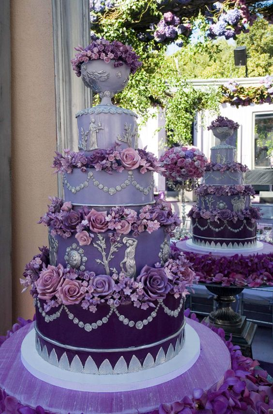 The couple's four-tiered wedding cake graduated in shades of purple from a rich plum on the bottom to a pastel lavender on top. Silver rosettes and cameos as well as real purple flowers decorated each tier. The cake sat on purple linen and the base was surrounded with purple orchids.