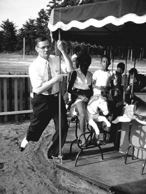 A white man riding along with African-American children on a small carousel in a segregated playground. Photograph by Margaret Bourke-White. Greenville, South Carolina, USA, 1956.: