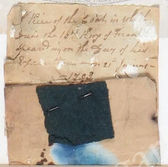 Fragment of the coat Louis XVI wore on the day of his execution, framed with an engraving of the King in prison writing his last will and testament.
