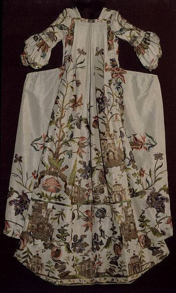 Cream silk sack-back and petticoat made from a mantua from the late 1730s. The fabric is embroidered with polychrome silks and gold thread in floral and gothic motifs, including architectural buildings and structures. Large peonies sprout from the roof of a ruined abbey flanked by pine trees, dominating a landscape set with three different cottages, cedar trees replete with cones, a Chinoiserie fence, and a pavilion with a flag flying, alternating with a giant flowering creeper: