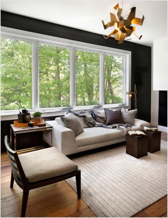 New york beige rug beige sofa black accent wall black wall chandelier ribbon windows side table unique chandelier wood floor