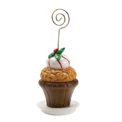 """Welcome guests to your holiday table with this sweet cupcake place card holder. The decorative cupcake is frosted and topped with mistletoe, and a metal holder rises from the middle. It can also be used to display holiday cards! Item weight: 0.1 lb. 2 1/2"""" x 2 1/2"""" x 5 1/4"""" high. Polyresin and metal."""
