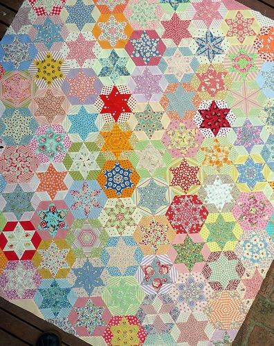 hexagon blocks are made using just one diamond shaped template to cut fabric pieces.  Most  fabrics were carefully fussy-cut to create a repeat pattern in the center star.  The quilt top is entirely hand pieced.: