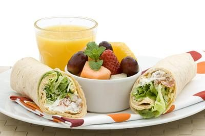 Veggie wrap with a side of fruit and orange juice