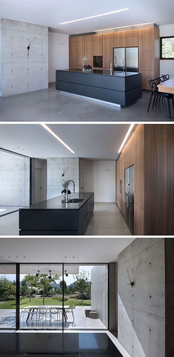 In this modern kitchen, minimalist wood cabinets line the wall, while a black island makes a statement. Next to the kitchen is a concrete wall adorned with a simple clock. #ModernKitchen #KitchenDesign