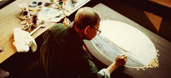 Artist at Ecustomfinishes creating a custom sailboat painting on dresser