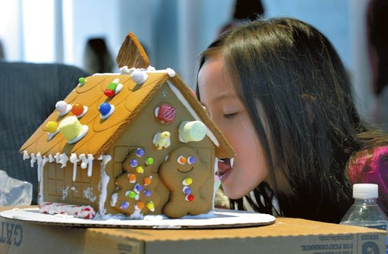 Five years old, Brannon Bell, can't resist licking the icing from the roof of her gingerbread house  at the Rowan Museum workshop.     photo by Wayne Hinshaw, for the Salisbury Post