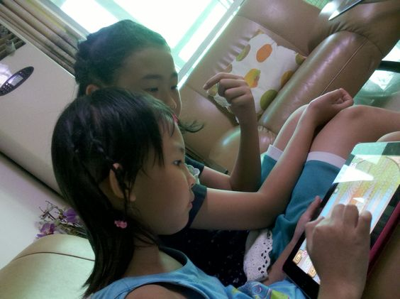 """<Any age>. My two cousins playing """"Moorland"""", a popular children-oriented social game on iPad. Are people getting access to social  media too early?"""