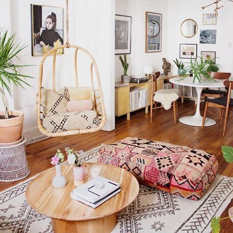 Rattan swing in boho chic apartment with pink accents.