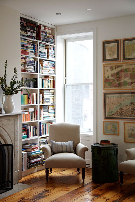 ample bookshelves, comfortable chair near a window and wall of framed maps make a great reading corner in living room of 'A Farmhouse-Style Home in Brooklyn':