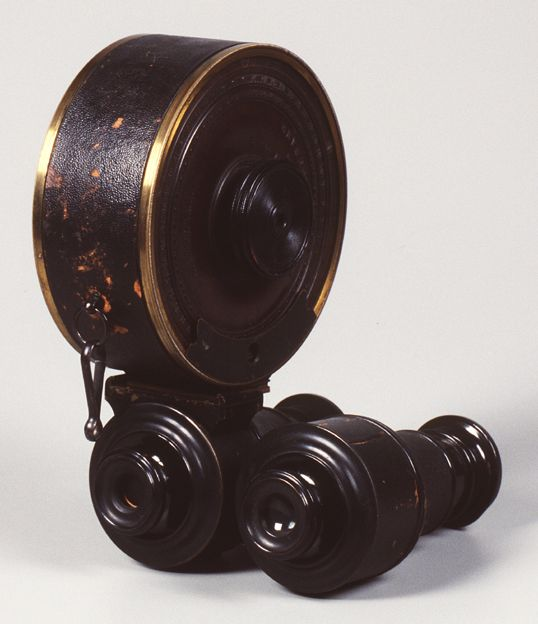 """c1867.  An early binocular-styled camera for 50 exposures on 1¼ x 1¼    in. plates.  A large cylindrical magazine contained the 50 ..."