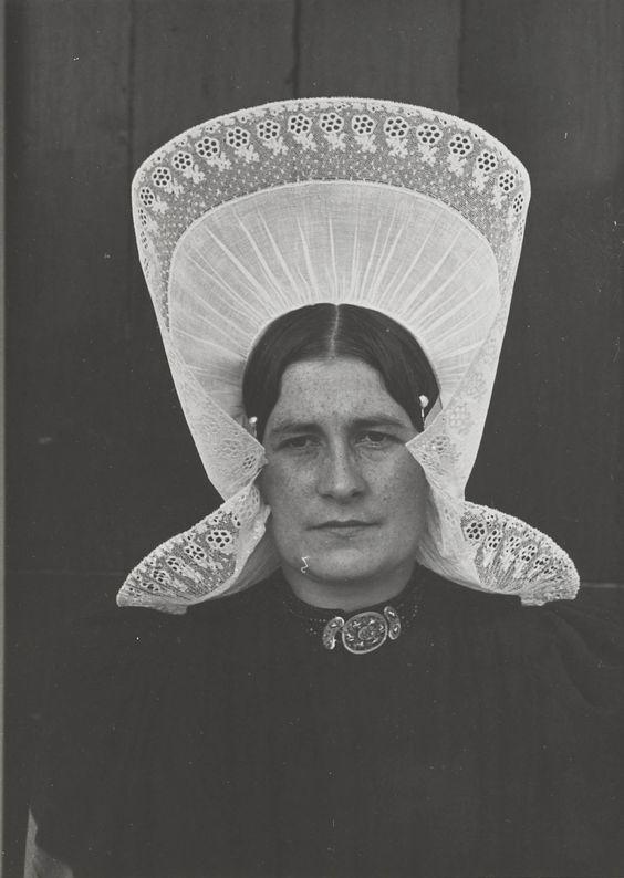 Vrouw uit Huizen in zondagse dracht. Ze draagt de oorijzermuts, die met hulp van een tweede persoon is opgezet. 1945 #NoordHolland #Huizen #oorijzermuts
