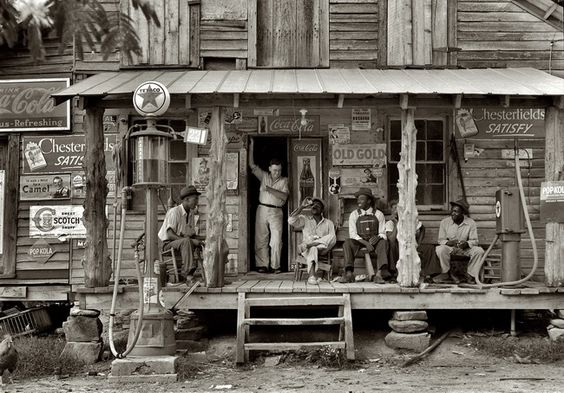 "Dorothea Lange - July 1939. Gordonton, N.C. ""Country store on dirt road. Sunday afternoon. Note kerosene pump on the right and the gasoline pump on the left. Rough, unfinished timber posts have been used as supports for porch roof. Negro men sitting on the porch. Brother of store owner stands in doorway."""