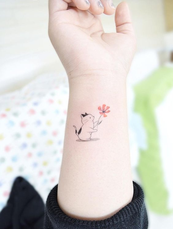 Cat holding a flower tattoo. Small tattoos are perfect for girls and women alike. Delicate and feminine, I promise these 28 blissfully small tattoos will not disappoint. Enjoy!: