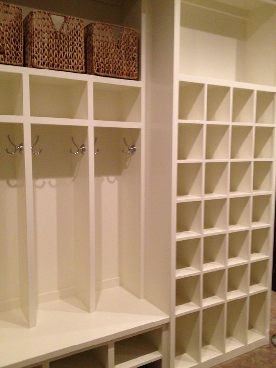 This mud room has open cabinets. A lot of shoe storage area. White colour is making area big. We can see vertical horizontal lines. Rectangle and Square shape on cabinet. Spacious and modern .