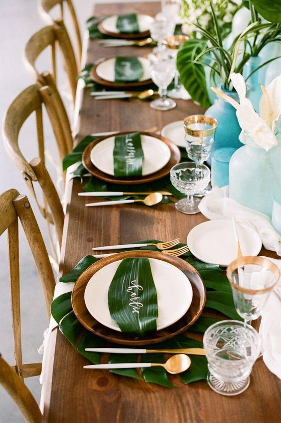 Decoração tropical para o carnaval com mesa de madeira e folhagens.