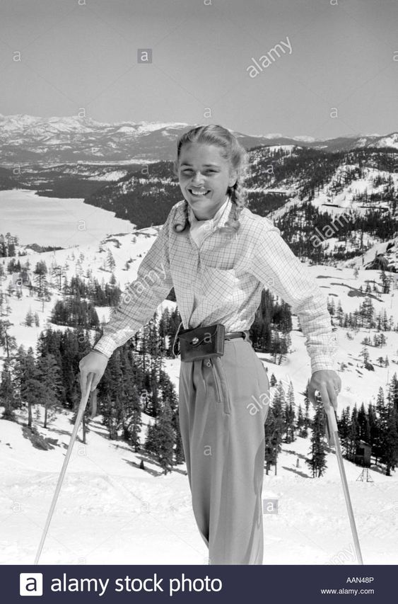 Download this stock image: 1940s 1950s YOUNG BLOND ATHLETIC WOMAN LOOKING AT CAMERA SMILING STANDING WITH SKI POLES TOP OF MOUNTAIN - AAN48P from Alamy's library of millions of high resolution stock photos, illustrations and vectors.