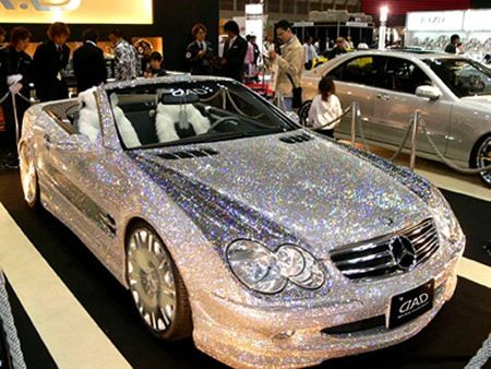 """Diamond-Covered Mercedes SL. The ultra-shiny, glitzy diamond covered Mercedes SL class was spotted at an auto show overseas. Though, there is no surety, if the diamonds are real, but, it looks really dazzling whatsoever! And if you want to estimate its value then you need to know your mathematics well….that is the place value of zeros beyond billions.""  I don't even know what to say about this except that it's iridescent, all right!"