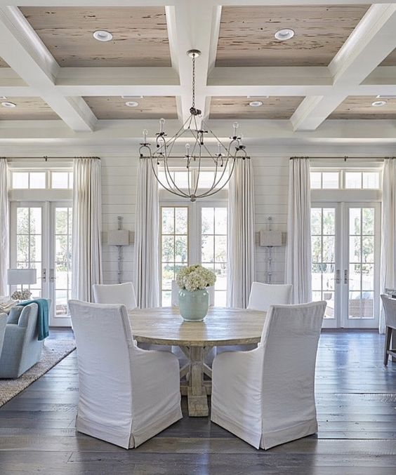 Gorgeous coffered ceiling in dining room with beachy, coastal, traditional style decor. The white slipcovered dining chairs around the rustic round table are so welcoming! #diningroom #beachhouse #cofferedceiling #coastaldecor #traditionaldecor