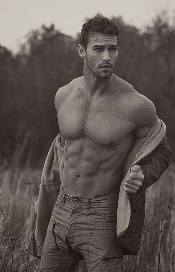 Model Jay Byars sexily removes his shirt in the middle of a field at sunset. (Thank you!):