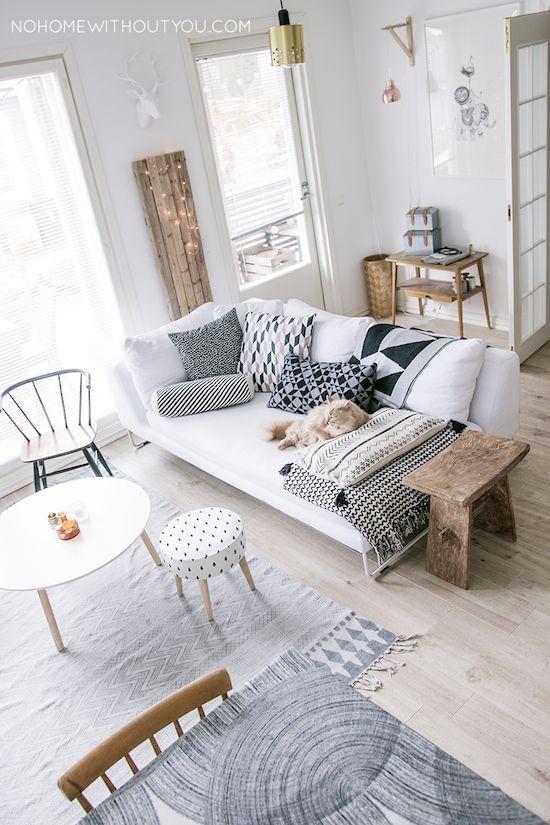 Ambiance scandinave dans la décoration de ce salon. Mur blanc, parquet en bois blond, ensemble de coussins: