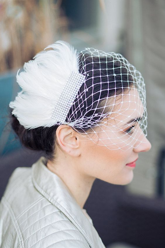 Cet ornement de coiffure pour la mariée allie le charme délicat d'une voilette à larges mailles, ponctuée de strass, avec le style glamour d'un