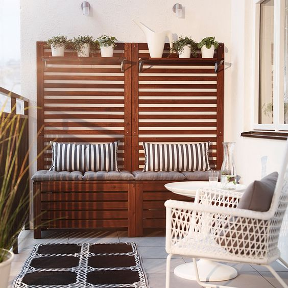 Ein Balkon mit ÄPPLARÖ Banktruhen mit Wandpaneel und Borden für Wandpaneel in Braun mit GRENÖ Kissen weiß gestreift, HÖGSTEN Sessel in Weiß,...