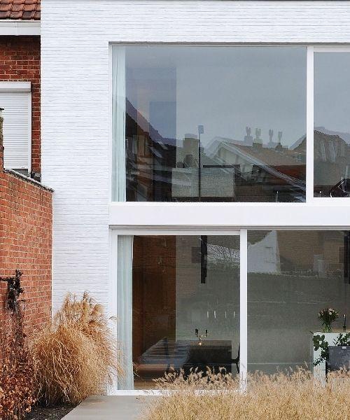 Deze rijwoning is afgeschermd voor de drukte, maar open naar het groen • Architect: Bettina Luyten (achtergevel • grote ramen • witte gevel • modern)
