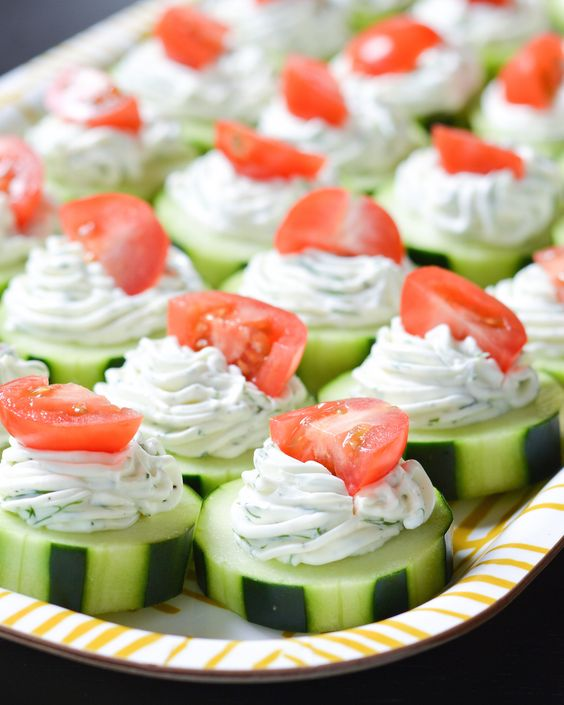 These fresh Dilly Cucumber Bites make a great healthy appetizer. Cucumber slices are topped with a fresh dill cream cheese and yogurt mixture, and finished with a juicy cherry tomato.: