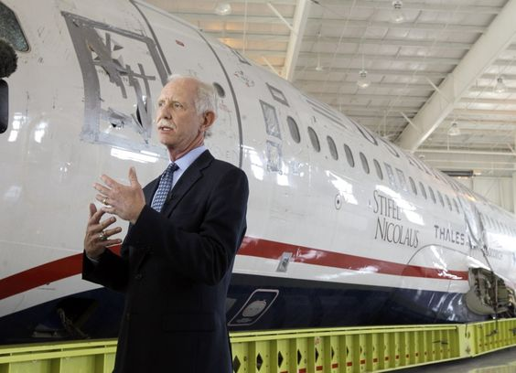 Capt. Chesley 'Sully' Sullenberger, and the fuselage of the plane he successfully ditched in the Hudson River - saving 155 lives.
