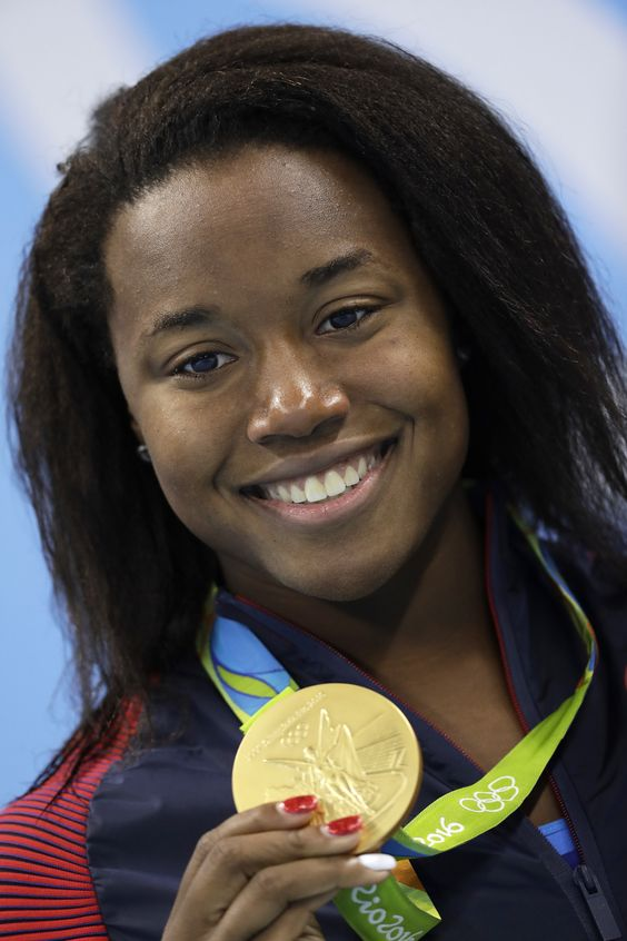 United States' Simone Manuel shows off her gold medal during the medal ceremony for the women's 100-meter freestyle final during the swimming competitions at the 2016 Summer Olympics, Friday, Aug. (AP Photo/Michael Sohn)