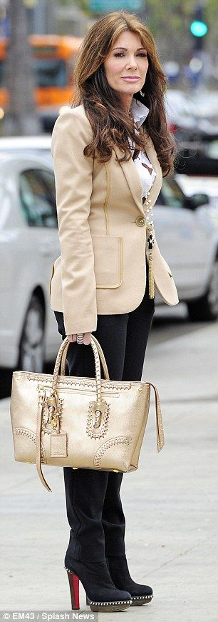 Lisa Vanderpump.. looking chic in black trousers and a beige blazer teamed with sky-high black boots.