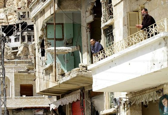 Syrian men stand on the balcony of a damaged building in the ancient Christian town of Maalula, located 56 kilometres northeast of the Syrian capital Damascus, as French tourists (unseen) take part in a visit of the town on April 8, 2015, during Easter celebrations. AFP PHOTO / LOUAI BESHARA        (Photo credit should read LOUAI BESHARA/AFP/Getty Images)