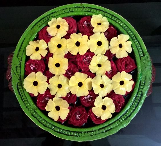 Yellow flowers arranged chess shape over red roses ..