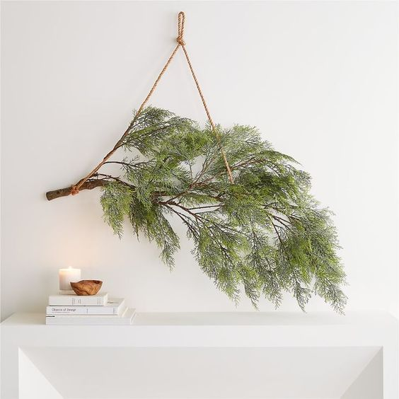 Simple Scandi Christmas decor - a prelit branch hung simply above a mantel - Crate and Barrel.