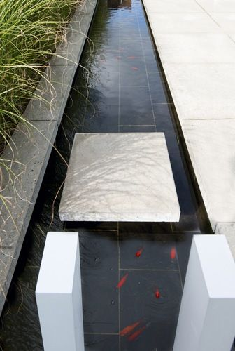 deep black rill against ivory stone and garden grasses