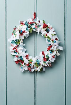 Christmas wreath using scraps of fabric. We've created ours using plain white cotton, festive prints and pretty glass beads, simply sewn and pinned onto a florist's moss ring.